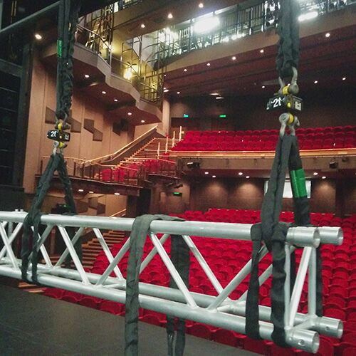 A truss hangs suspended above a stage with two load cells